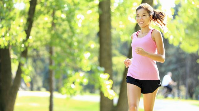 Das Bild zeigt eine junge Frau, die im Wald joggt.