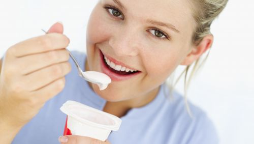 Das Bild zeigt eine Frau beim Joghurt essen.