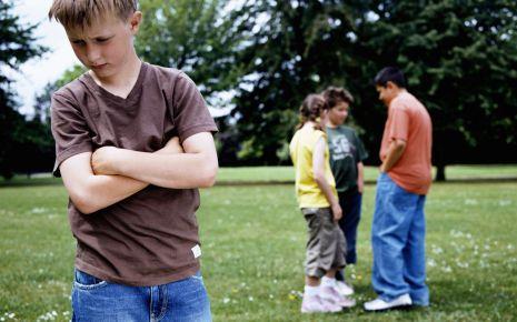 Ein Junge steht einsam und mit verschränkten Armen auf einer Wiese, im Hintergrund eine Gruppe Kinder.