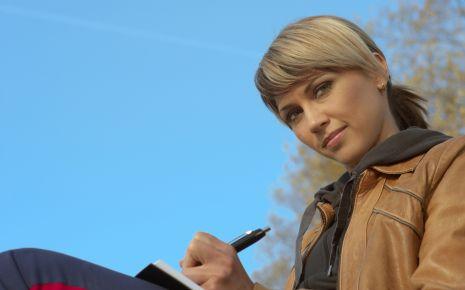 Eine junge Frau sitzt draußen und macht sich Notizen.