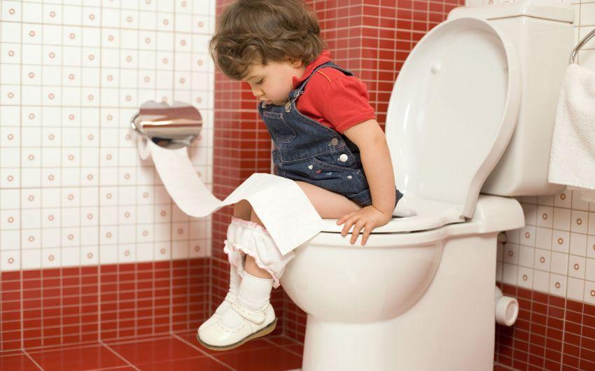Ein kleines Mädchen sitzt auf dem WC.