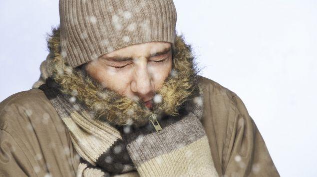 Mann mit Schal, Mütze und dicker Jacke kkneift die Augen zusammen.