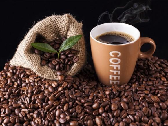 Man sieht Kaffeebohnen und eine Tasse Kaffee.