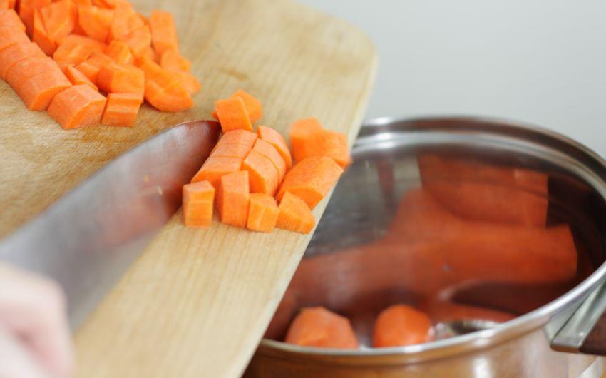 Durchfall: Jemand schiebt geschnittene Karottenstücke von einem Brotbrett in einen Kochtopf.