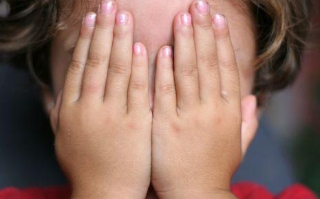 Ein Kind verdeckt seine Augen mit den Händen.