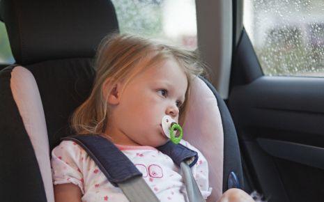 Man sieht ein Kind im Auto in einem Kindersitz.