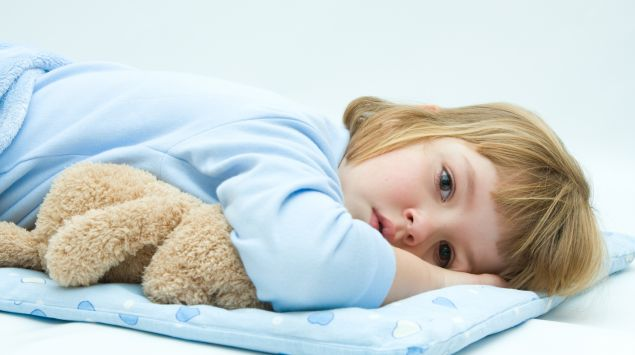 Man sieht ein krankes Mädchen mit seinem Teddy.