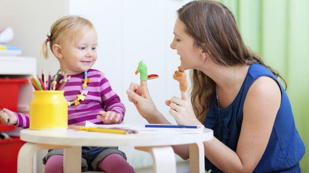 Das Bild zeigt eine Frau, die mit einem Mädchen spielt.