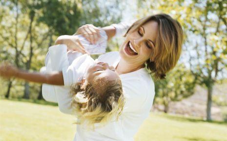 Man sieht eine Mutter, die ihre Tochter im Freien durch die Luft wirbelt.