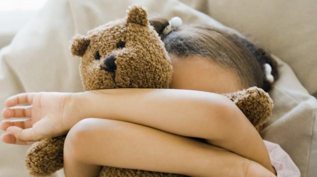 Das Bild zeigt ein Mädchen mit Teddy vor dem Gesicht.