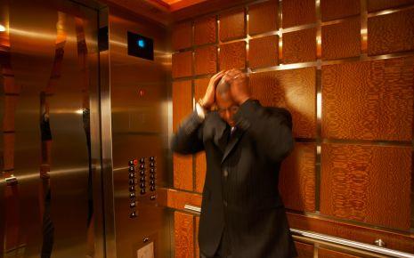 Ein Mann im Fahrstuhl schlägt vor Angst die Hände über dem Kopf zusammen.