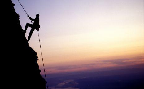 Das Bild zeigt einen Mann, der einen Berg hochklettert.
