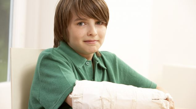 Das Bild zeigt einen Jungen mit Gipsarm.