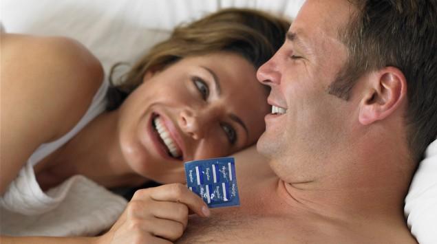 Das Bild zeigt ein Paar im Bett, die Frau hält ein Kondom in der Hand.