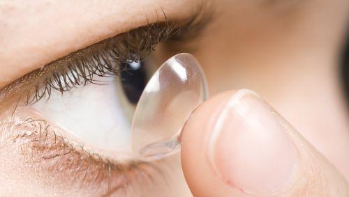 Eine Frau setzt sich eine Kontaktlinse ein.