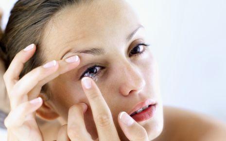 Das Bild zeigt eine Frau, die sich eine Kontaktlinse einsetzt.
