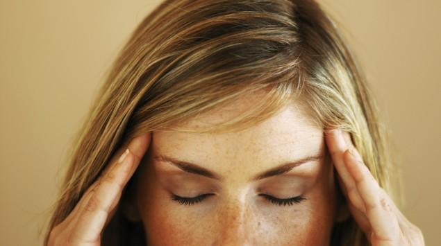 Das Bild zeigt den oberen Teil des Kopfes einer Frau, die sich die Schläfen hält.