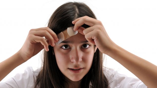 Das Bild zeigt ein Mädchen, das sich ein Pflaster auf die Stirn klebt.