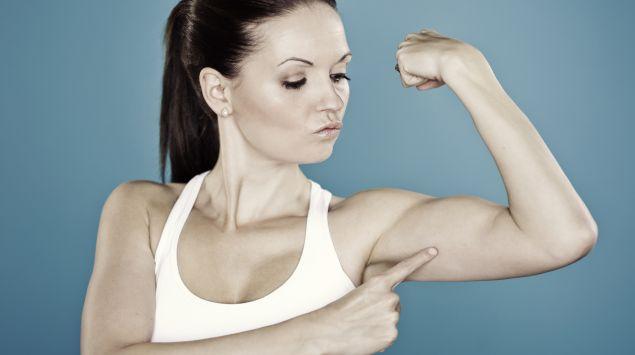 Das Bild zeigt eine Frau, die auf ihren Armmuskel zeigt.