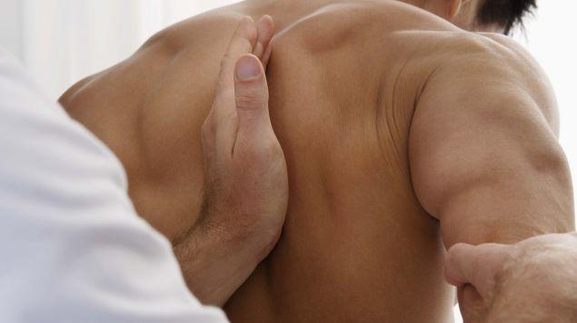Ein Krankengymnast arbeitet im Schulterbereich eines Patienten.