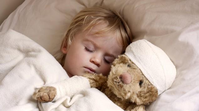Man sieht ein krankes Kind im Bett mit einem Teddy, der einen Verband um den Kopf trägt.