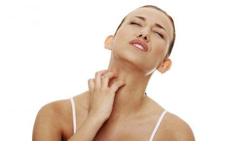 Eine Frau kratzt sich am Hals.