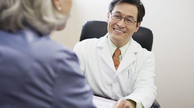 Ein lächelnder Arzt im Gespräch mit einer Patientin.