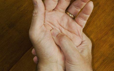 Kribbeln in den Händen: Ein Mand drückt mit dem Daumen der rechten auf die Innenfläche seiner linken Hand.