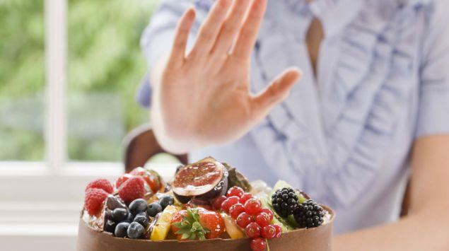 Eine Frau lehnt mit einer Handbewegung das ihr angebotene Essen ab.