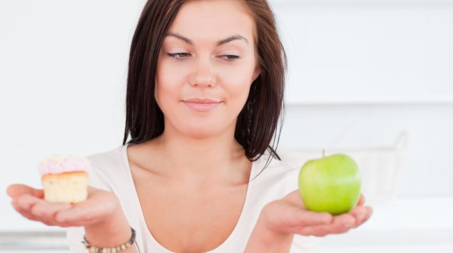 Man sieht eine Frau, die in einer Hand ein Stück Kuchen hält, in der anderen einen Apfel.