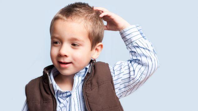 Das Bild zeigt einen Jungen, der sich an den Kopf greift.