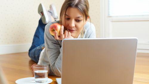 Eine Frau liegt auf dem Boden und schaut auf ihren Laptop, sie hält einen Apfel in der Hand, neben ihr steht ein Glas Wasser.
