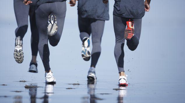 Man sieht die Bein von vier Läufern, die am Strand joggen, von hinten.