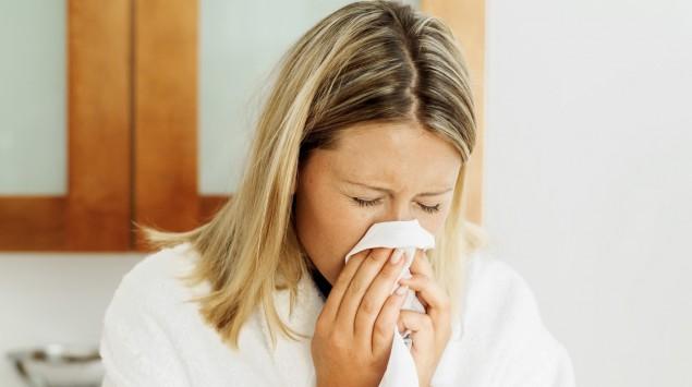 Das Bild zeigt eine Frau, die Nase putzt.