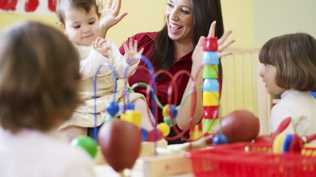 Das Bild zeigt eine Frau, die mit Kindern spielt.