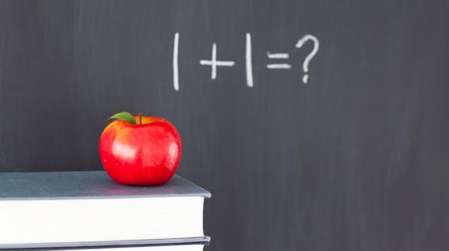 Das Bild zeigt einen Apfel vor einer Tafel.