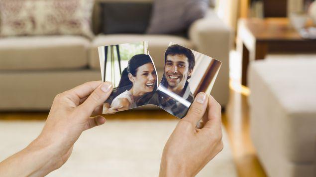 Jemand zerreißt ein Foto, auf dem ein junges Paar zu sehen ist.