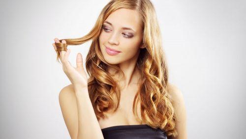Eine junge Frau wickelt eine Haarsträhne um den Finger.