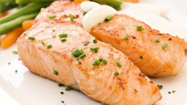 Das Bild zeigt einen teller mit gekochtem Fisch und Gemüse.