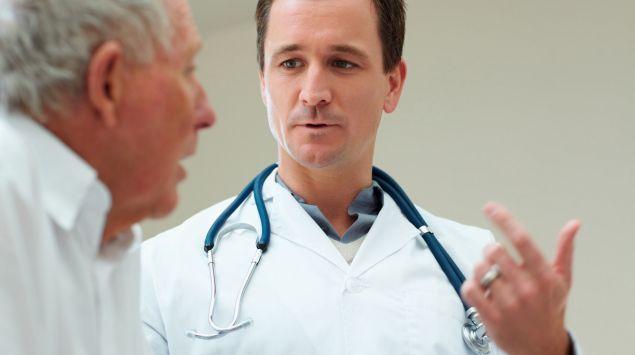 Das Bild zeigt einen Arzt im Gespräch mit einem älteren Patienten.