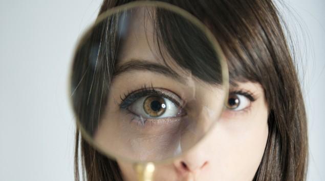 Eine Frau blickt mit dem rechten Auge durch eine Lupe in die Kamera.
