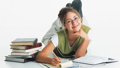 Ein junges Mädchen liegt auf dem Boden und lernt, neben ihm ein Stapel Bücher.