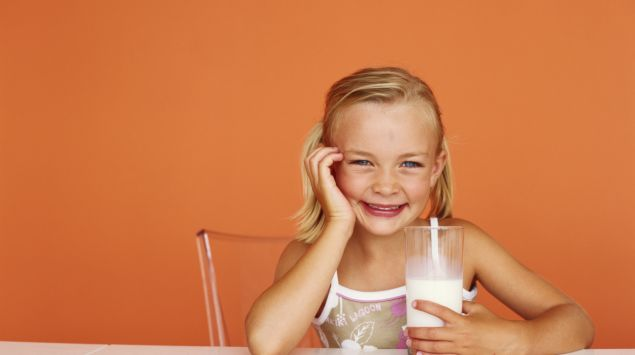 Ein kleines Mädchen sitzt am Tisch und hat ein Glas Milch in der Hand.