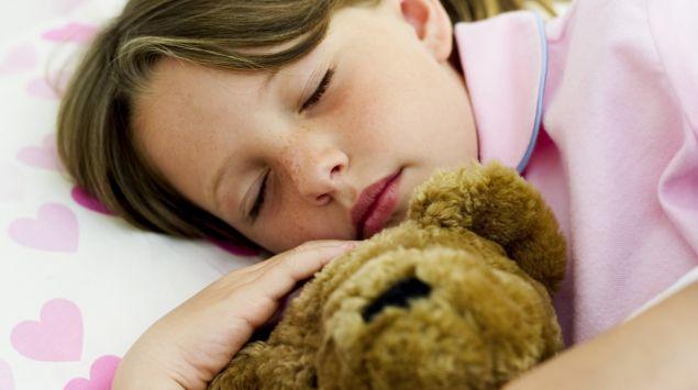 Ein Mädchen schläft im Bett und hält einen Teddy im Arm.