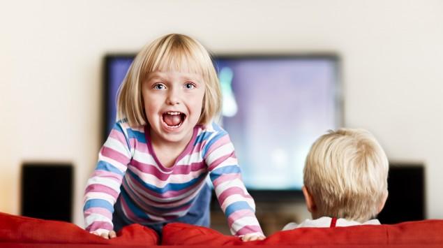 Ein blondes Mädchen tobt auf dem Sofa, neben ihr sitzt ein Junge, der TV schaut.