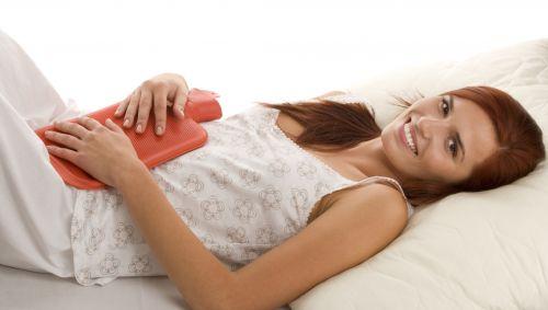 Das Bild zeigt eine Frau, die im Bett liegt und eine Wärmflasche auf ihrem Bauch festhält.