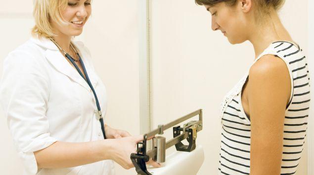 Das Bild zeigt eine Ärztin, die eine Patientin wiegt.