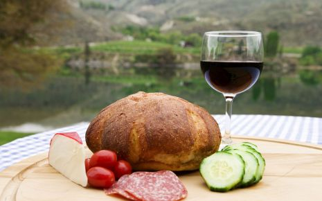 Man sieht einen Laib Brot, Käse, Tomaten, Gurken, Salami und ein Glas Rotwein.