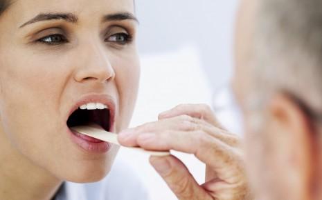 Halsschmerzen: Das Bild zeigt einen Arzt, der eine Patientin untersucht.