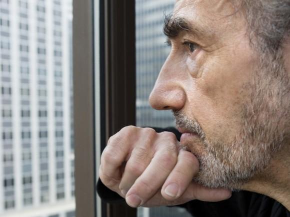Ein Mann schaut nachdenklich aus dem Fenster eines Hochhauses.
